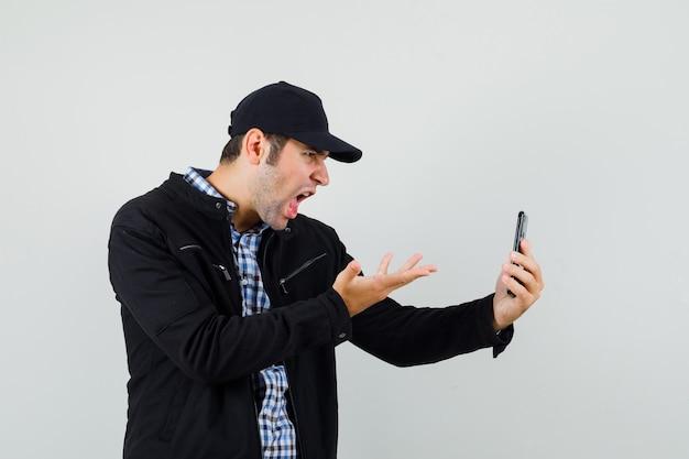 Giovane uomo in camicia, giacca, berretto che discute di qualcosa in chat video e sembra arrabbiato
