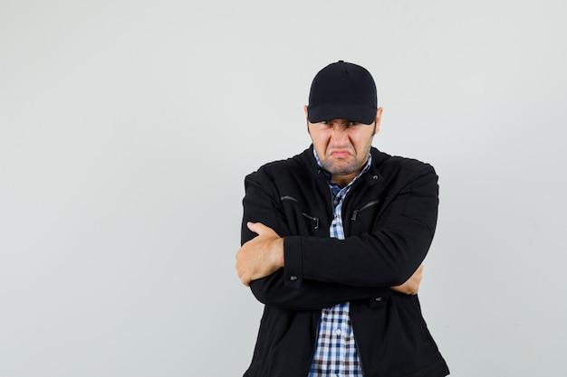 Giovane uomo in camicia, giacca, berretto in piedi con le braccia strettamente incrociate e guardando risentito