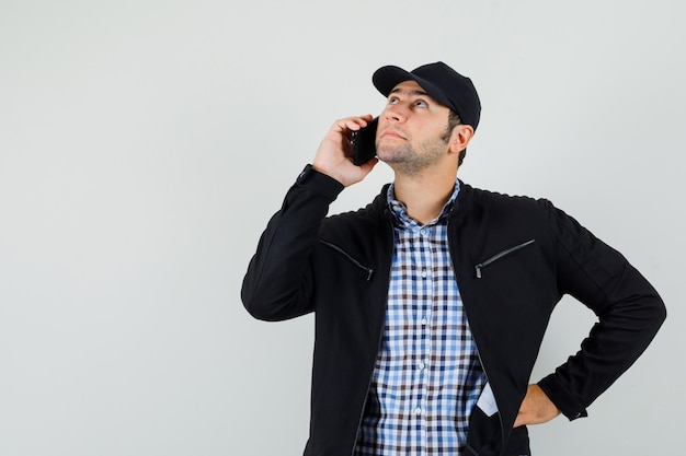 Young man in shirt, jacket, cap talking on mobile phone and looking pensive