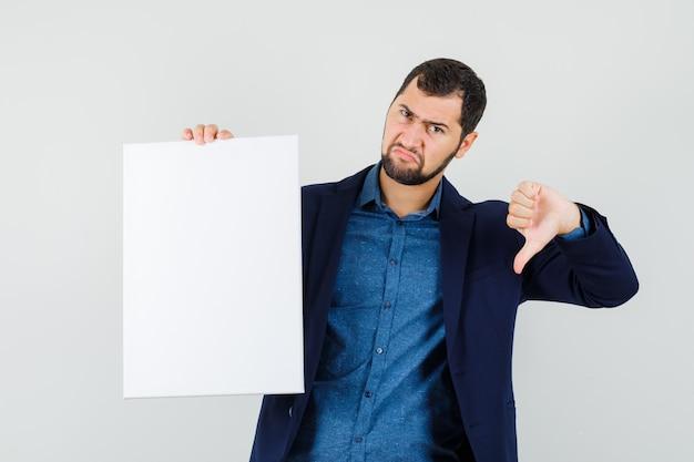 Giovane uomo in camicia, giacca in possesso di tela bianca, mostrando il pollice verso il basso e guardando il malcontento, vista frontale.