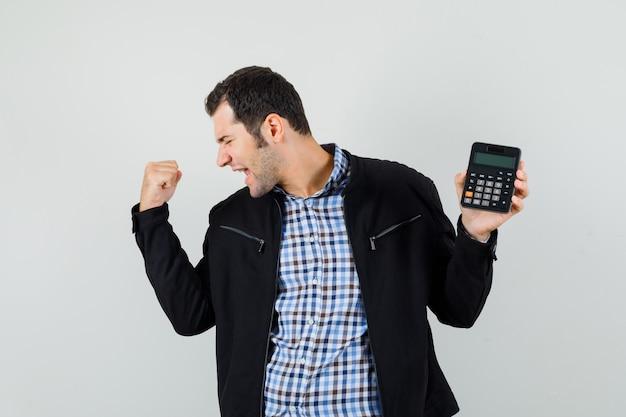 Giovane uomo in camicia, giacca azienda calcolatrice, mostrando il gesto del vincitore e guardando felice