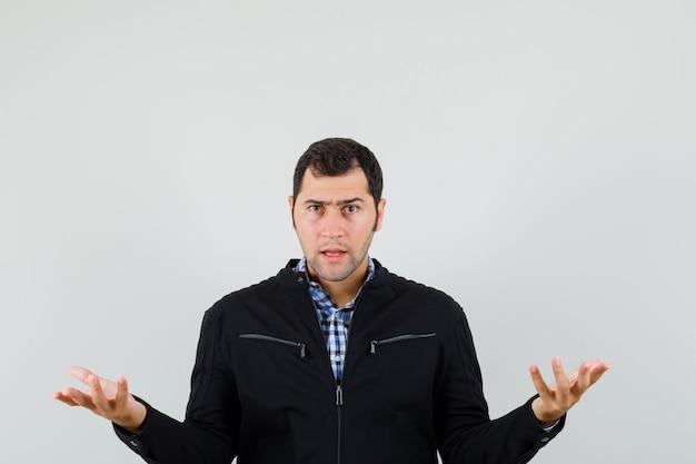 Giovane uomo in camicia, giacca tenendo le mani nel gesto interrogativo e guardando serio