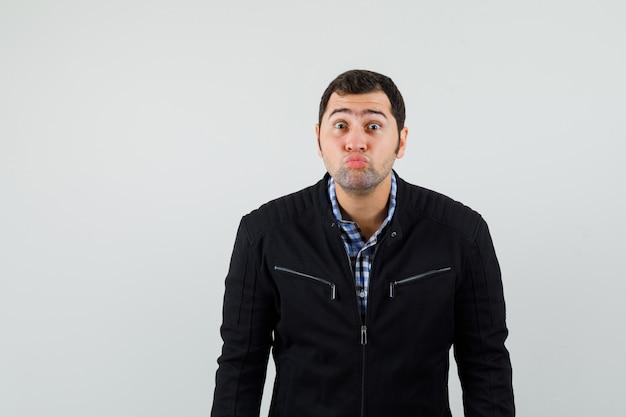 Giovane uomo in camicia, giacca mantenendo le labbra piegate e guardando divertente