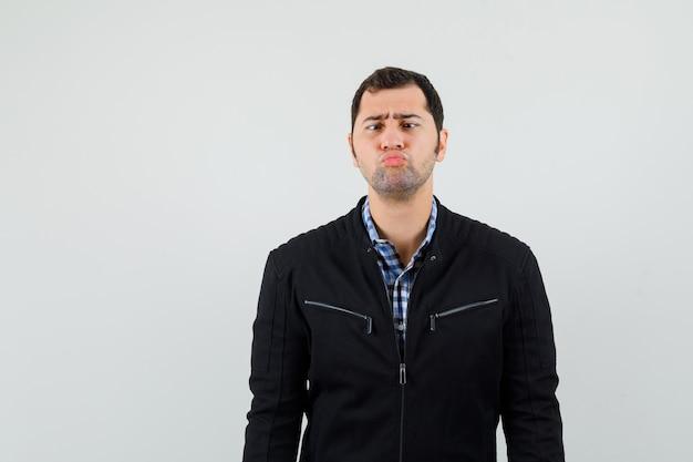 Giovane uomo in camicia, giacca mantenendo le labbra piegate e guardando cupo