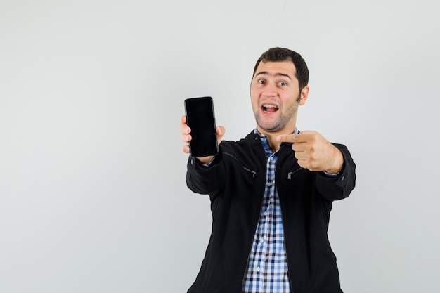 Young man in shirt, jacket pointing at mobile phone and looking jolly