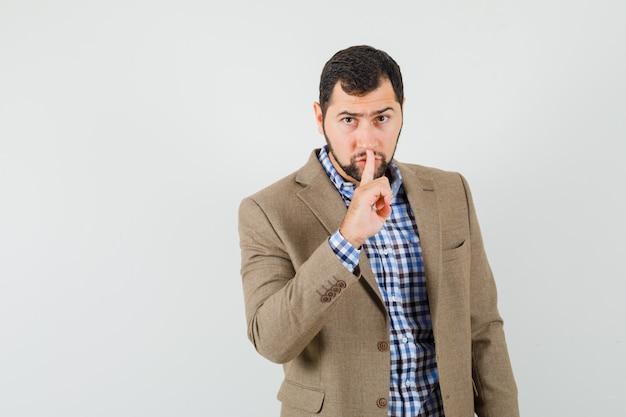 Giovane uomo in camicia, giacca che mostra gesto di silenzio e guardando attento, vista frontale.