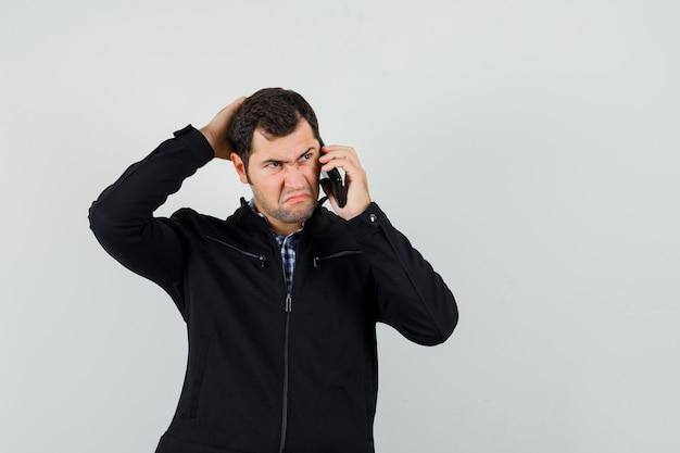 Giovane uomo in camicia, giacca parlando al telefono cellulare e guardando pensieroso