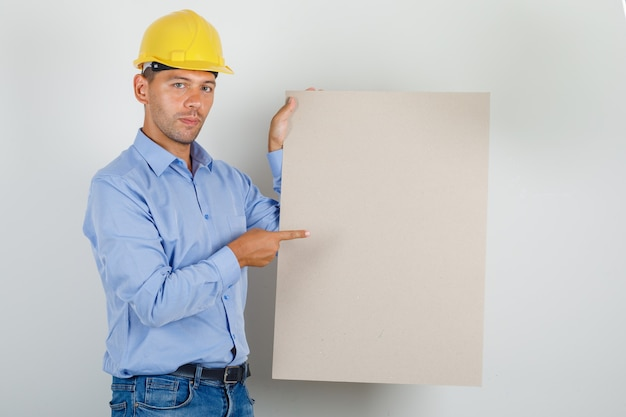 Young man in shirt, jeans, helmet pointing finger at canvas