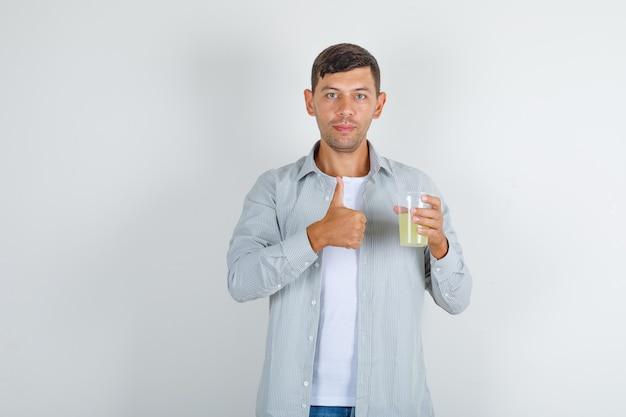 Giovane uomo in camicia, jeans che tengono il bicchiere di succo con il pollice in su