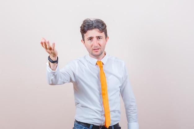Giovane in camicia, jeans alzando la mano in un gesto perplesso