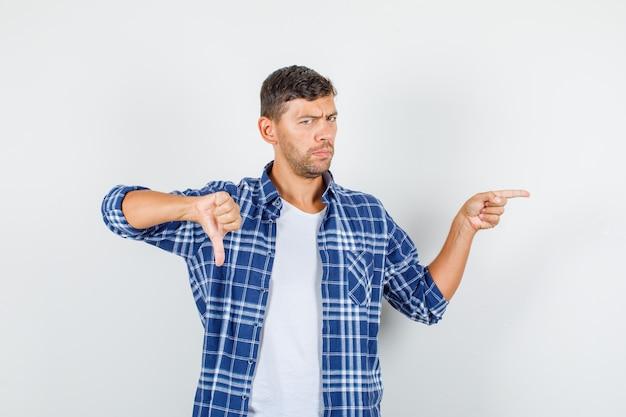 Giovane uomo in camicia che punta lontano con il pollice verso il basso e guardando scontento, vista frontale.