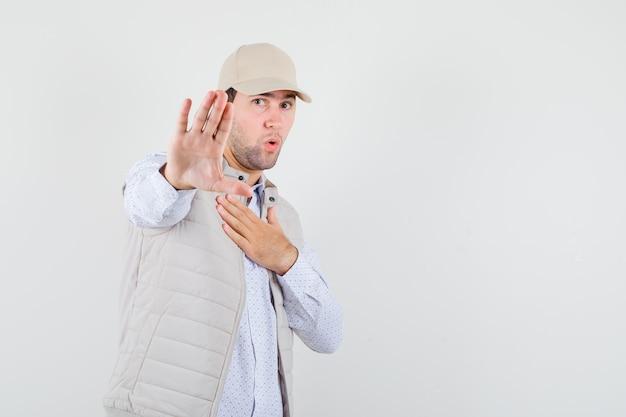 Giovane uomo in camicia, giacca senza maniche, berretto alzando la mano mentre rifiuta qualcosa e sembra riluttante, vista frontale.
