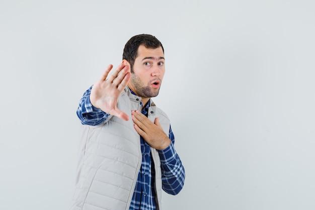 Giovane uomo in camicia, giacca senza maniche che rifiuta qualcosa, vista frontale.