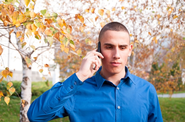 Young man in a shirt talking on the phone
