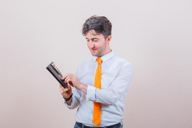 Giovane in camicia, cravatta, jeans che tira fuori la carta dal portafoglio e sembra ottimista