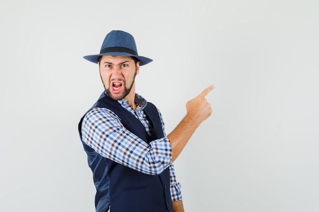 Giovane uomo in camicia, gilet, cappello rivolto lontano mentre urla e sembra arrabbiato, vista frontale.