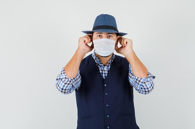 Giovane uomo in camicia, gilet, cappello che indossa una maschera medica e guardando attento, vista frontale.