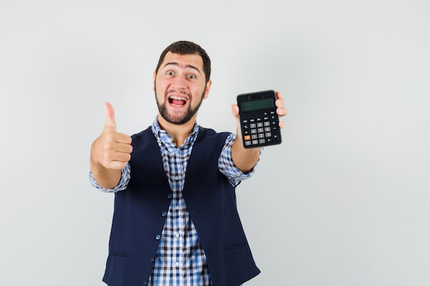 Young man in shirt, vest holding calculator, showing thumb up and looking blissful