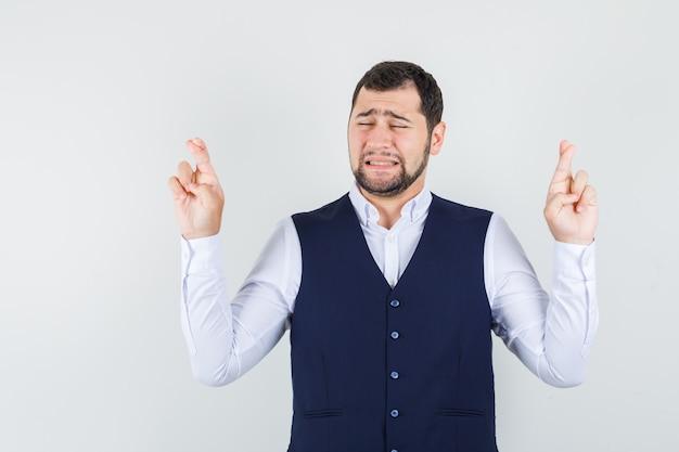 Giovane uomo in camicia, giubbotto tenendo le dita incrociate e guardando speranzoso