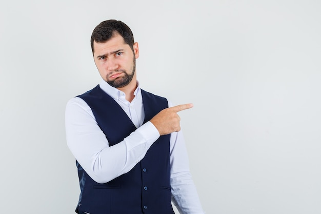 Young man in shirt, vest pointing away to complain and looking offended