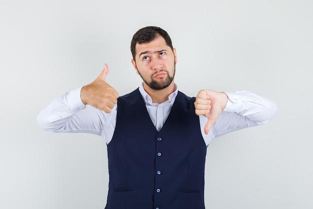 Giovane uomo in camicia, giubbotto che mostra i pollici su e giù e guardando pensieroso