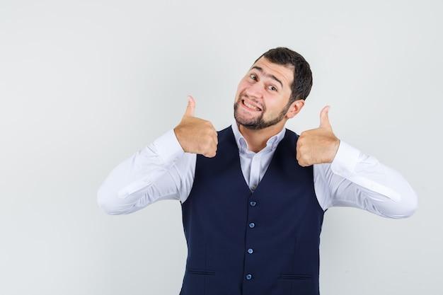 Giovane uomo in camicia, giubbotto che mostra i pollici in su e sembra allegro
