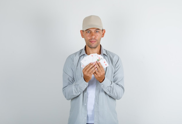 Young man in shirt with cap holding playing cards and smiling