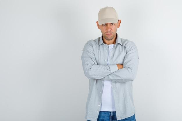 Giovane uomo in camicia con cappuccio, jeans in piedi con le braccia incrociate e guardando risentito