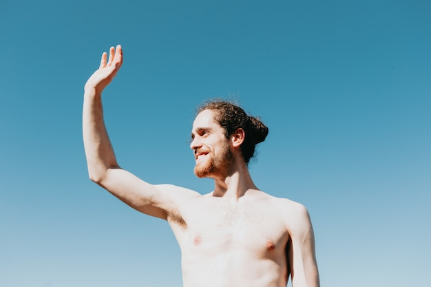 Young man shirtless on the beach saluting someone, clear background, liberty confidence concepts, holiday, beard and long hair