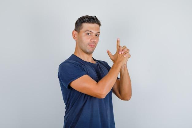 Молодой человек стреляет из пальчикового пистолета в синей футболке, вид спереди.