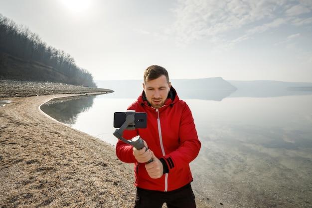 若い男が川沿いの電子スタビライザーで電話でビデオを撮影