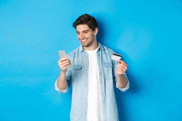 Giovane che fa shopping online con l'applicazione mobile, tiene in mano smartphone e carta di credito, in piedi su sfondo blu