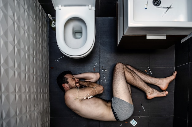Young man in shorts lying on floor alone in rest room. he scream and suffer. guy takes drugs. strong addiction. young man's hand in wrapped with plait. he hold it with hands. medicine on floor.
