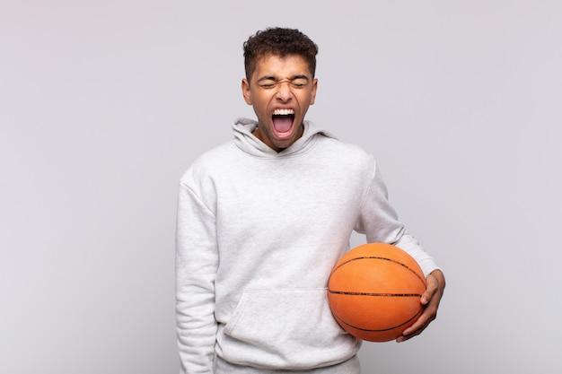 若い男は積極的に叫び、非常に怒っている、イライラしている、憤慨している、またはイライラしているように見え、ノーと叫びました。バスケットコンセプト