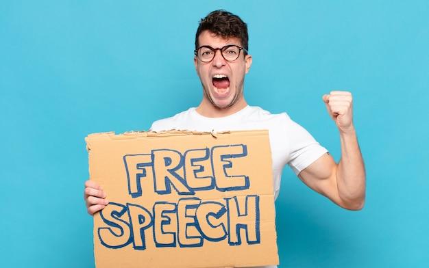 Молодой человек агрессивно кричит с гневным выражением лица или со сжатыми кулаками, празднуя успех