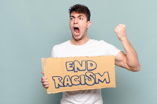 화난 표정으로 공격적으로 외치는 젊은 남자 또는 성공을 축하하는 주먹을 쥐고