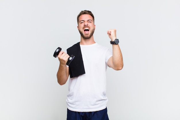 Young man shouting aggressively with an angry expression or with fists clenched celebrating success