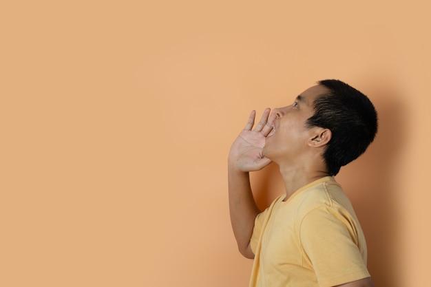 若い男は、オレンジ色のスタジオの背景に分離された口に手を置いて大声で叫び、叫んでいます。