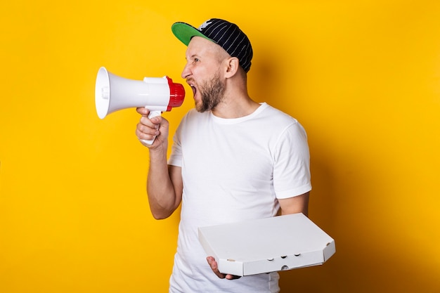 Young man shouting into a megaphone holding packed pizza on a yellow surface.