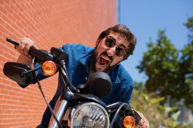 Young man shouting on a motorbike