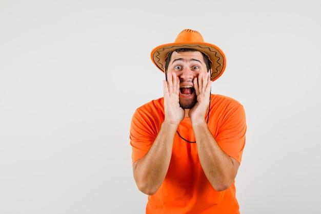 젊은 남자가 외치거나 오렌지 티셔츠, 모자에 뭔가를 발표하고 흥분을 찾고 있습니다. 전면보기.