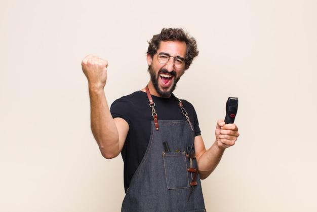 젊은 남자가 의기 양양하게 외치고, 흥분되고, 행복하고, 놀란 승자처럼 보이며, 축하합니다.
