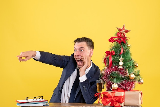 クリスマスツリーと黄色の贈り物の近くのテーブルに座って叫んでいる若い男