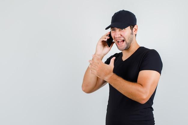 黒のtシャツでスマートフォンで話している間叫んでいる若い男