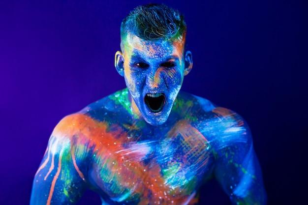 Молодой человек кричит. флуоресцентная краска на лице и мускулистый торс, в студии, снятый ультрафиолетовым светом