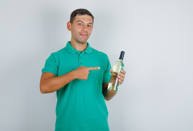 Молодой человек показывает бутылку алкоголя и улыбается в вид спереди зеленой футболке.