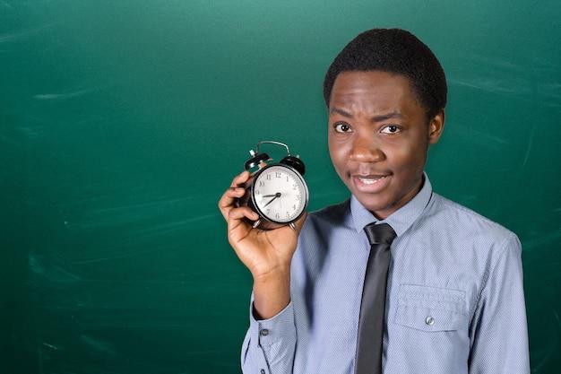 Молодой человек показывает будильник