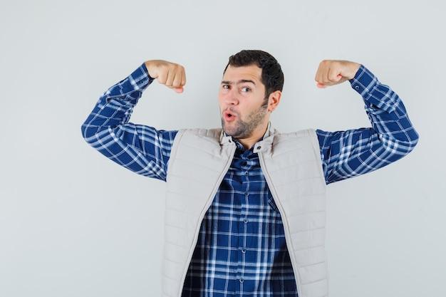 Молодой человек показывает мышцы рук в рубашке, безрукавке и выглядит гибким. передний план.