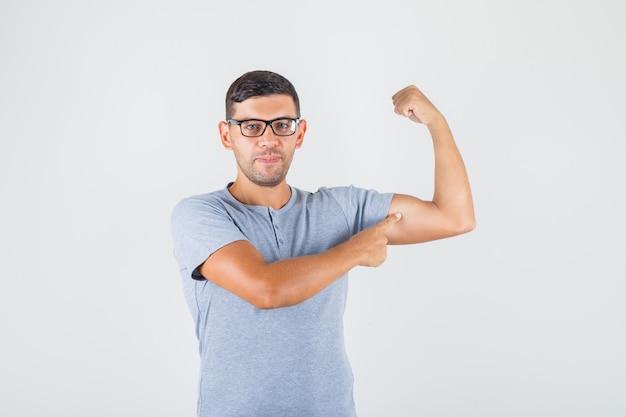 若い男が彼の腕に上腕二頭筋を灰色のtシャツ、メガネで表示