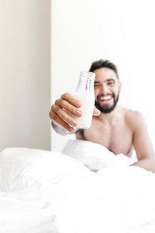 Young man showing bottle of milk